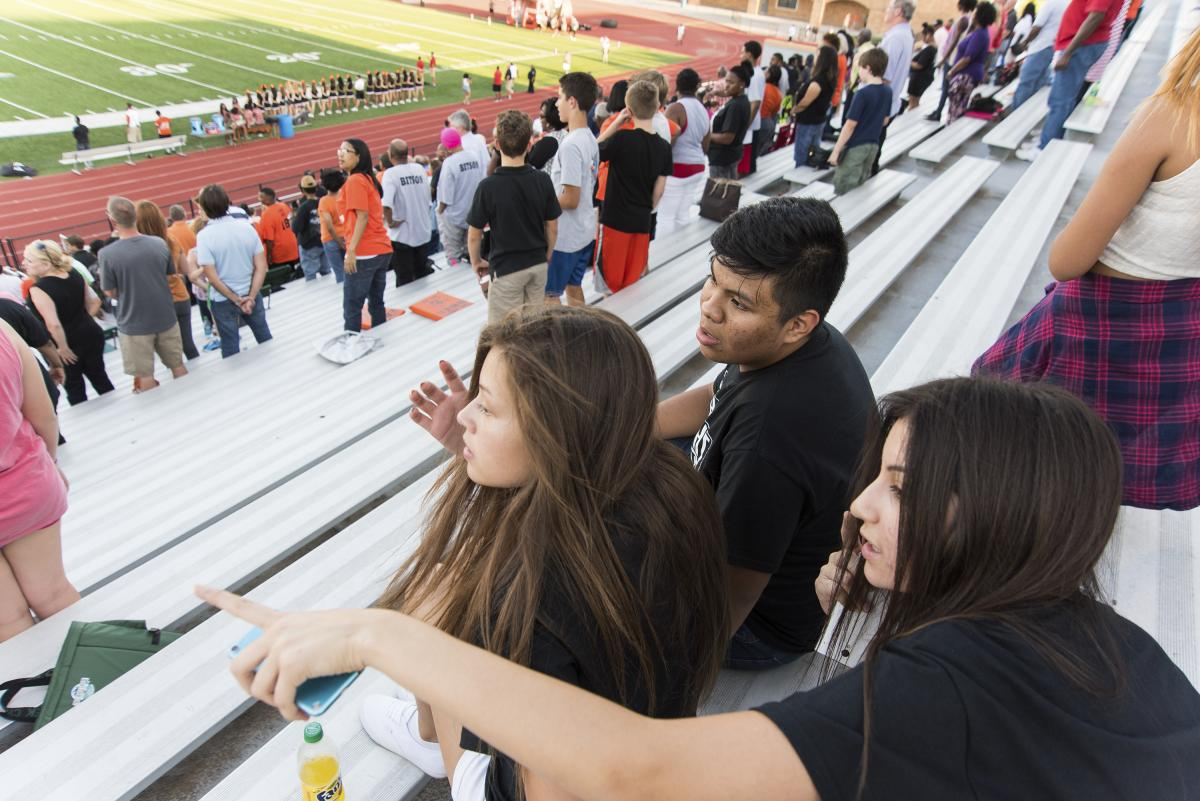 Jose and his friends Giovana Flores (left) and Anahi Macias sit and wait for the first home football game of the season to kickoff at S.E. Williams Stadium in Tulsa, Okla. All three students recently started their freshman year at Booker T. Washington Hig