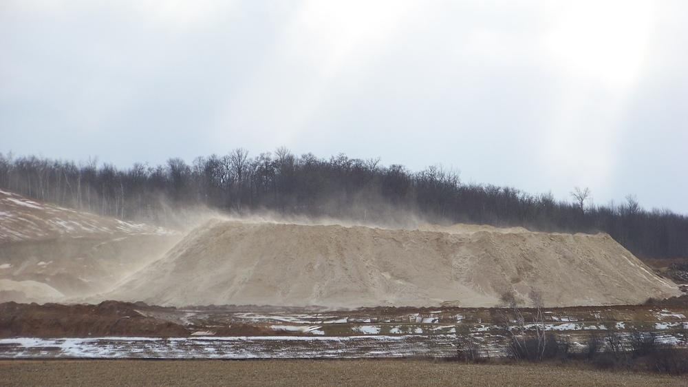 Dust blows off a pile of fracking sand at a mine near Chippewa Falls, Wis., on Dec. 15, 2011. Some of the air samples the National Institute for Occupational Safety and Health experts collected at fracking sites had such high levels of silica that the res