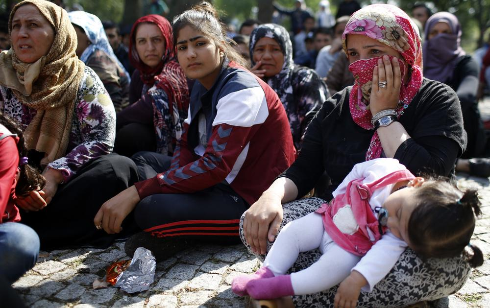 Migrants listen to a speaker talk to them about their future as they rest in a stadium while waiting to cross from Turkey's western border into Greece and Bulgaria on Wednesday.