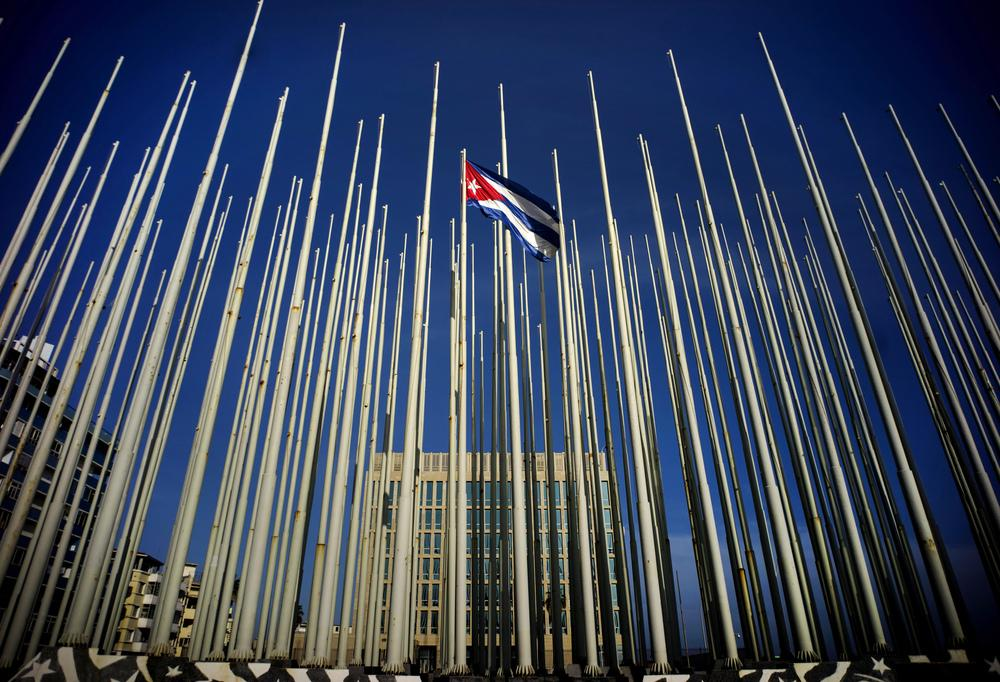 A Cuban flag flies among empty flag polls that obscure the then U.S. Interests Section. That building has again become the U.S. Embassy in Havana.