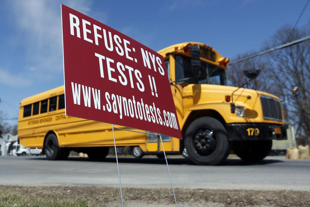 New York: A school bus passes a sign encouraging parents to refuse to let their children take state tests in Rotterdam, N.Y.