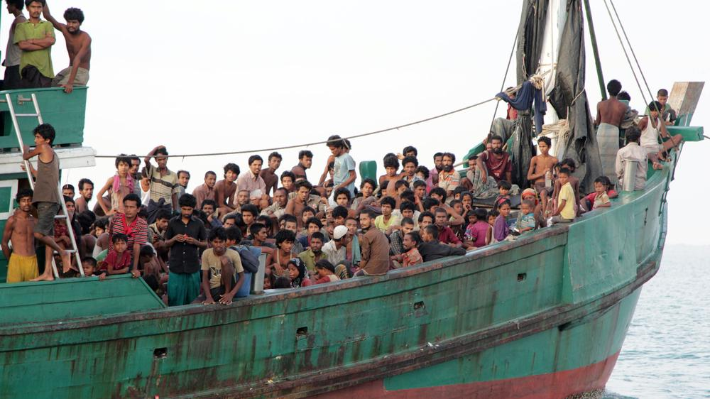 Migrants sit on their boat as they wait to be rescued by fishermen off East Aceh, Indonesia, on May 20. Thousands of Rohingya migrants have fled Myanmar and many have been stranded at sea as part of the growing migrant crisis in Southeast Asia.