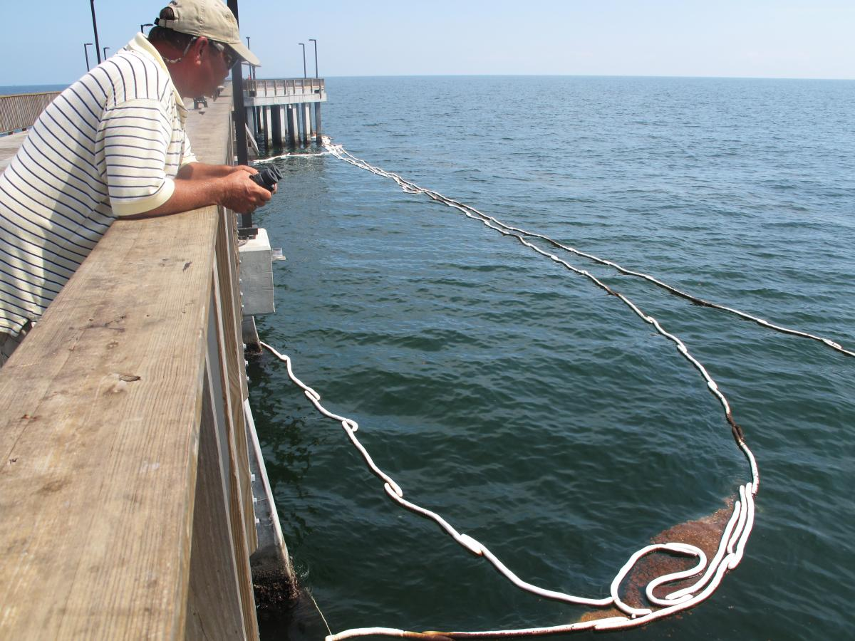 Wetzel Wood of Orange Beach, Ala., looks out at oil fouling the Gulf of Mexico during the BP oil spill five years ago. Absorbent boom was deployed around the Gulf State Park Fishing Pier to collect the oil for cleanup.