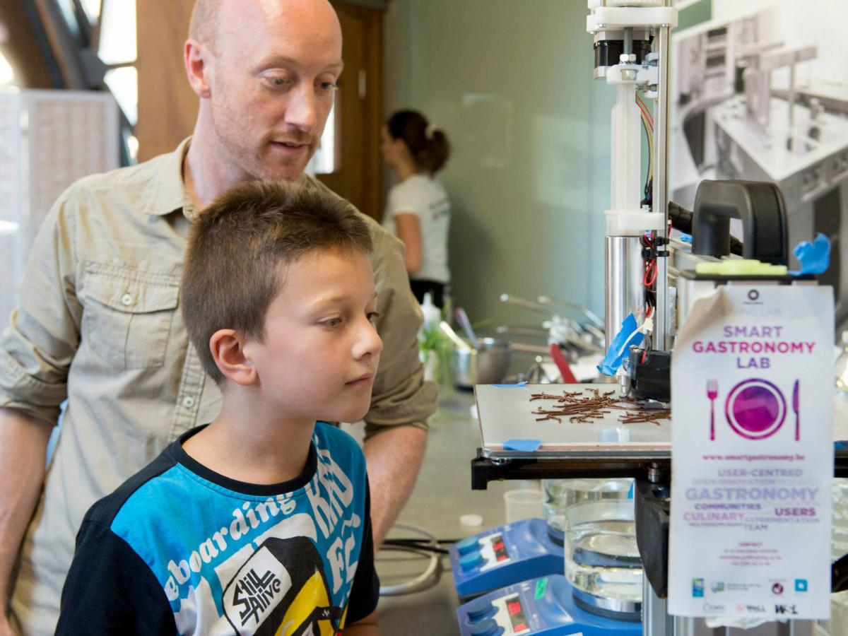 Lab visitors watch a 3-D printer squirt chocolate into an intricate shape designed by chef Arabelle Meirlaen.
