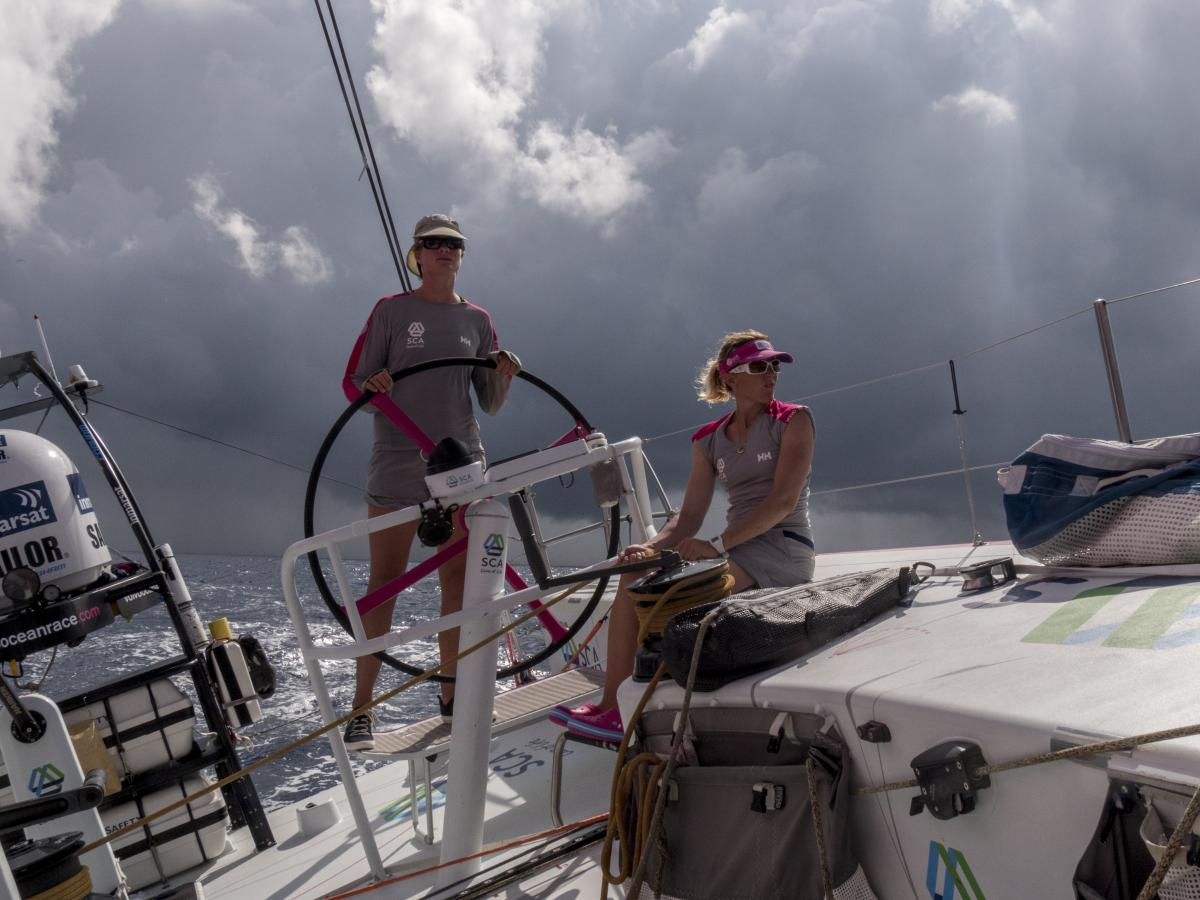Leg 2 onboard Team SCA, in November 2014. Elodie Mettraux helms and Sam Davies trims main as a squal passes behind the boat.