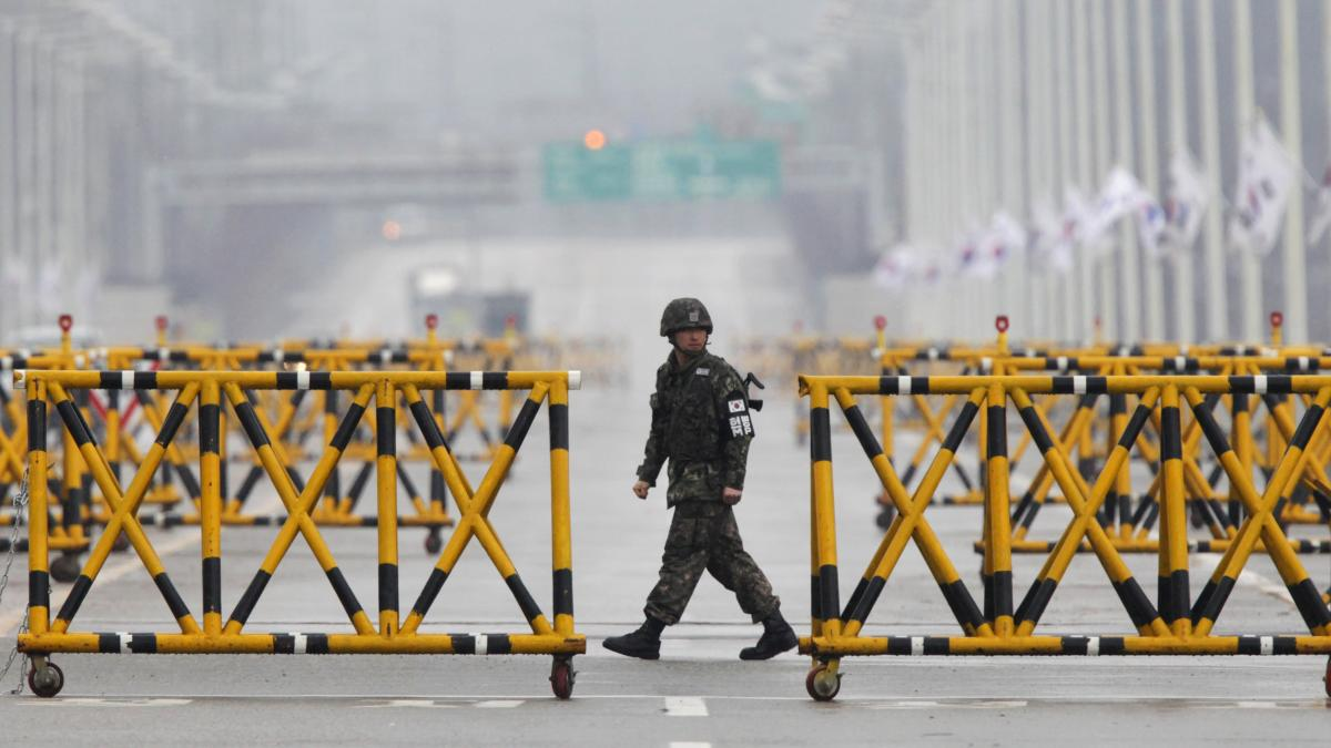 A South Korean soldier patrols as vehicles returning from the jointly run Kaesong industrial complex in North Korea arrive at a checkpoint in Paju, north of Seoul, on April 6.