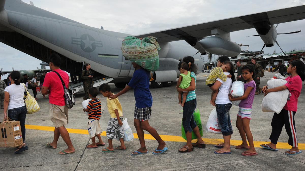 Survivors of Typhoon Haiyan line up to board a U.S. military C-130 plane headed for Manila. The plane arrived in Tacloban, Philippines, with relief supplies on Nov. 11.