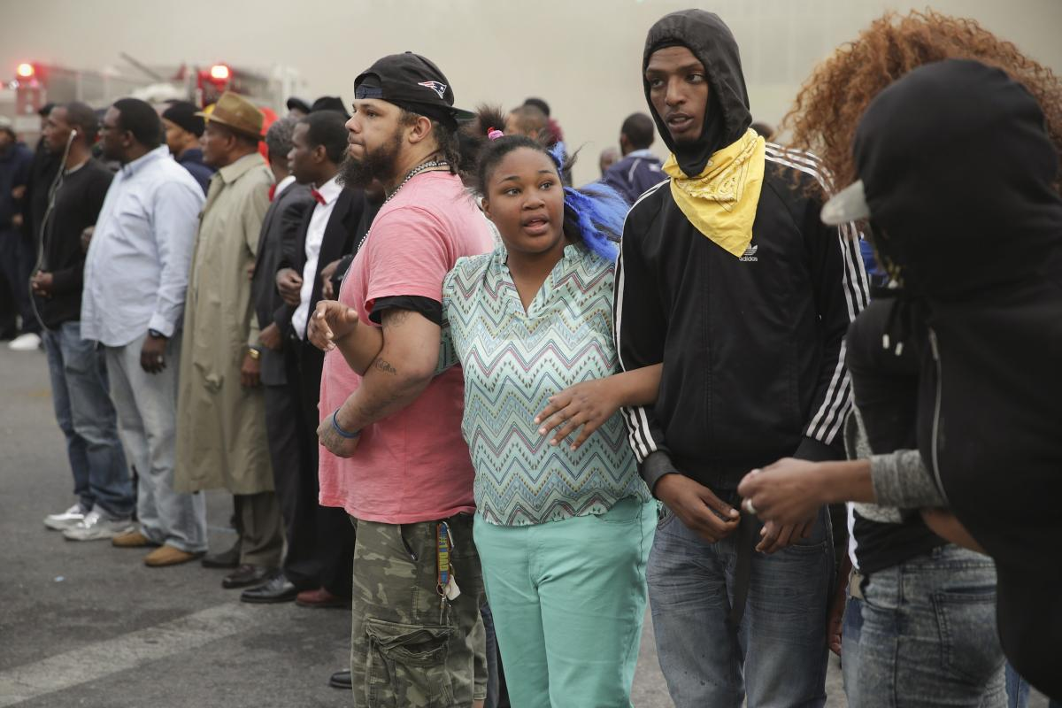 Baltimore residents lock arms and form a line opposing police during protests at the corner of Pennsylvania and North avenues.