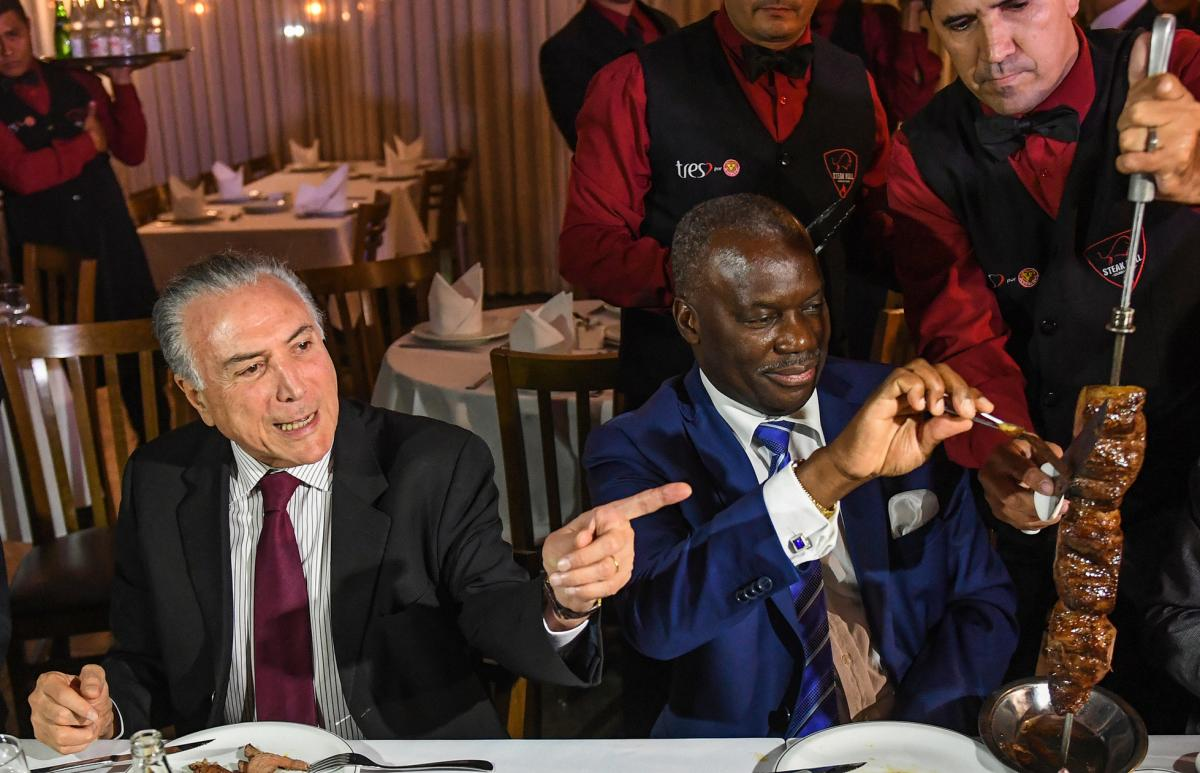 Brazil's President Michel Temer, left, held a dinner at a churrascaria in Brasilia to reassure ambassadors, such as Angola's Nelson Manuel Cosme, that the meat their countries are buying is of high quality.