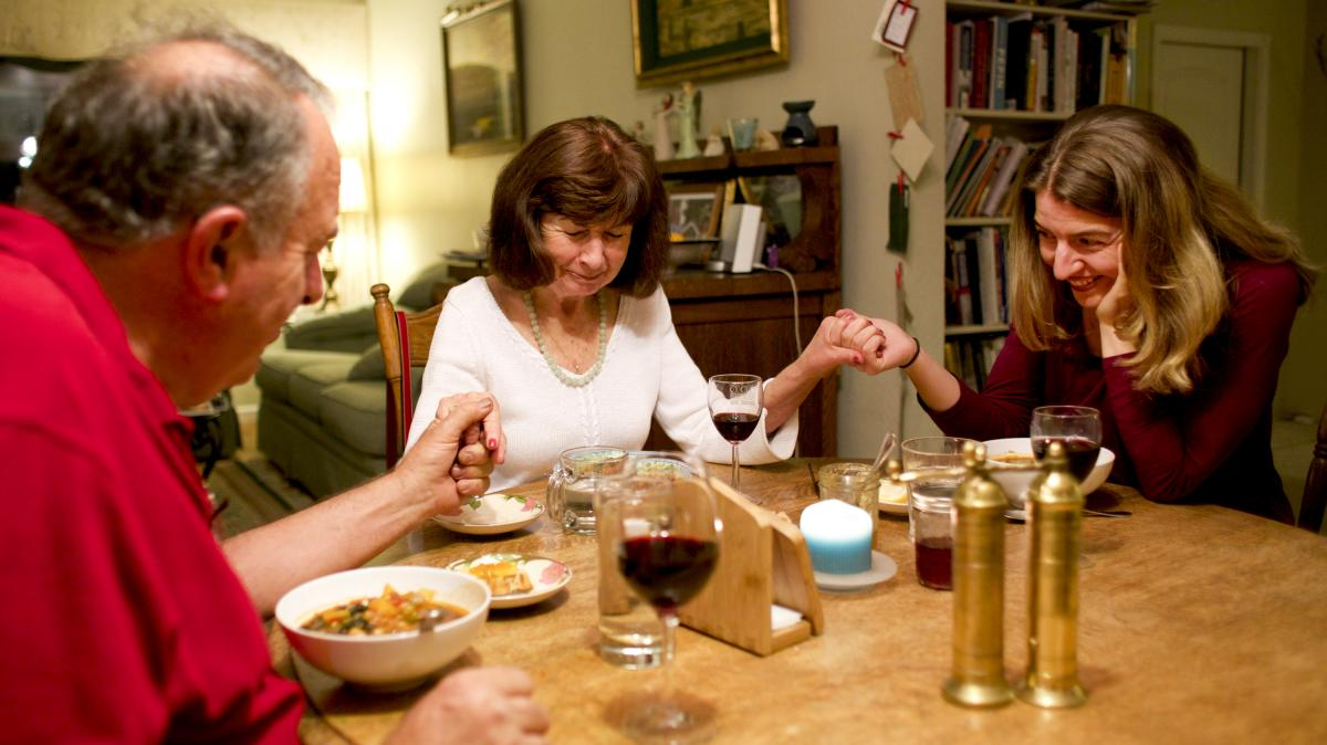 Marianne leads Rick and daughter Laurel, one of the couple's three adult children, in prayer before a meal together.
