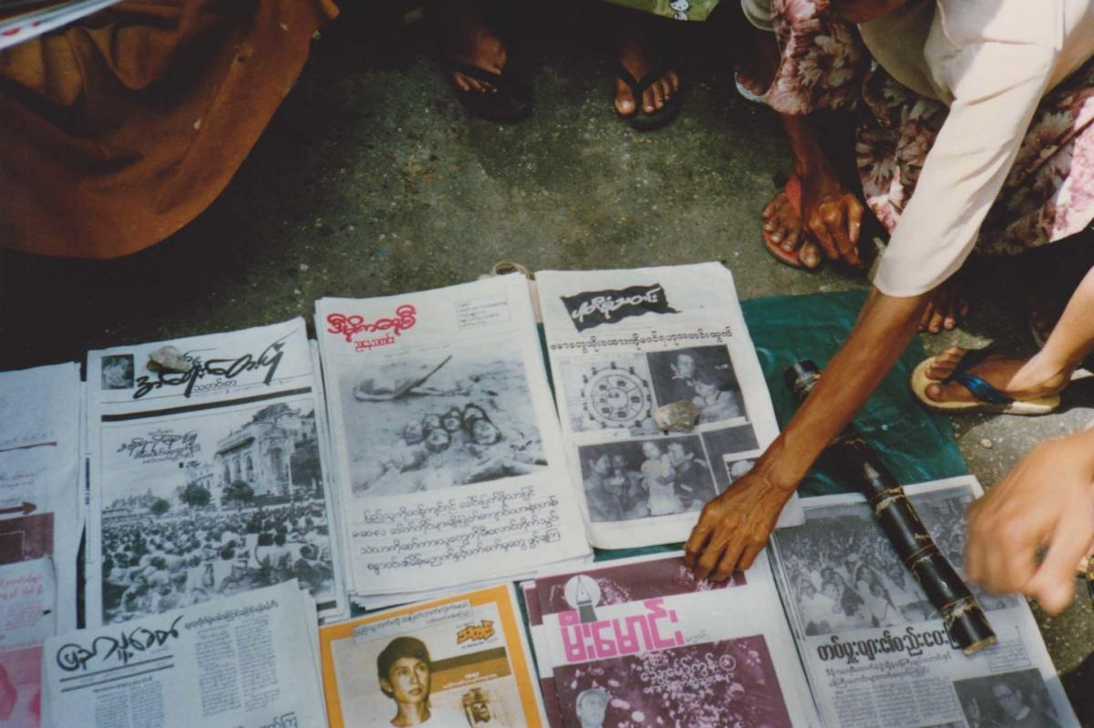 As momentum grew, activist newspapers suddenly entered a space previously filled only by government propaganda. One here includes a photo of Aung San Suu Kyi. After the September crackdown, her image was not seen on newsstands again until government censo