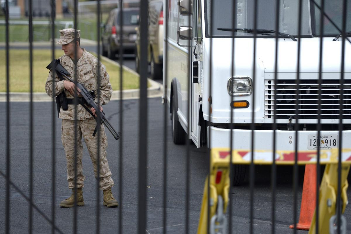 A military guard stands at the scene of the shooting. Shots were fired at around 8:20 a.m. ET.