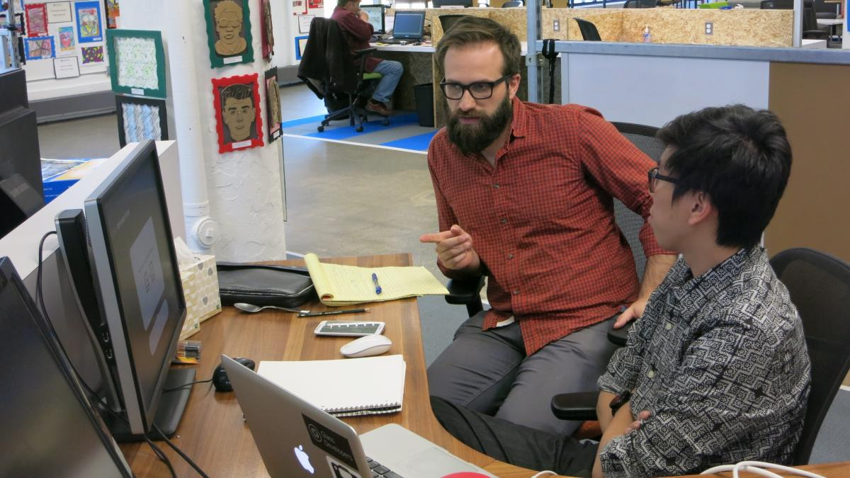 Adam Leeb (left), co-founder of Hemingwrite, and contractor Andrew Ku work in the common space area in TechTown Detroit, a nonprofit business incubator.