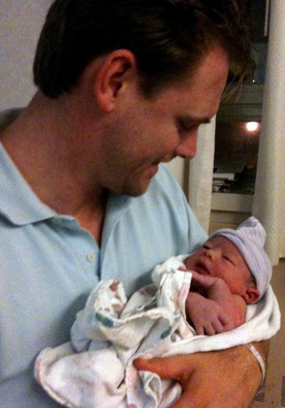 Kristian Aspelin cradles his newborn son, Johan.