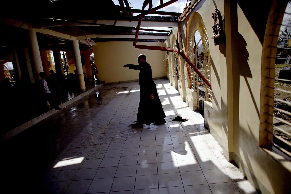 The Rev. Kelvin Apurillo of San Joaquin Parish, outside Tacloban, enters the battered parish church to celebrate Mass on Nov. 19.