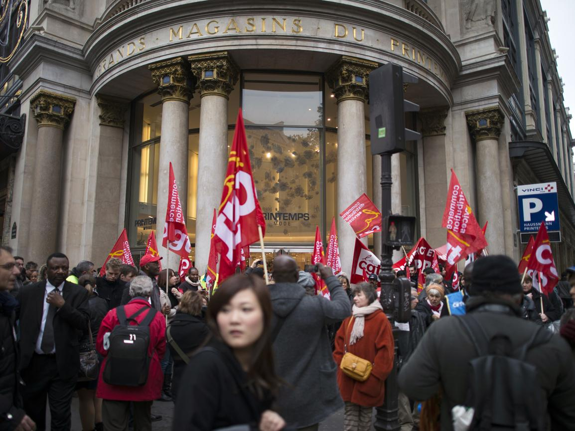 Dozens of trade union members and workers demonstrate in front of an open shopping mall in Paris last year. Labor groups are leading the push to keep the ban on Sunday work.