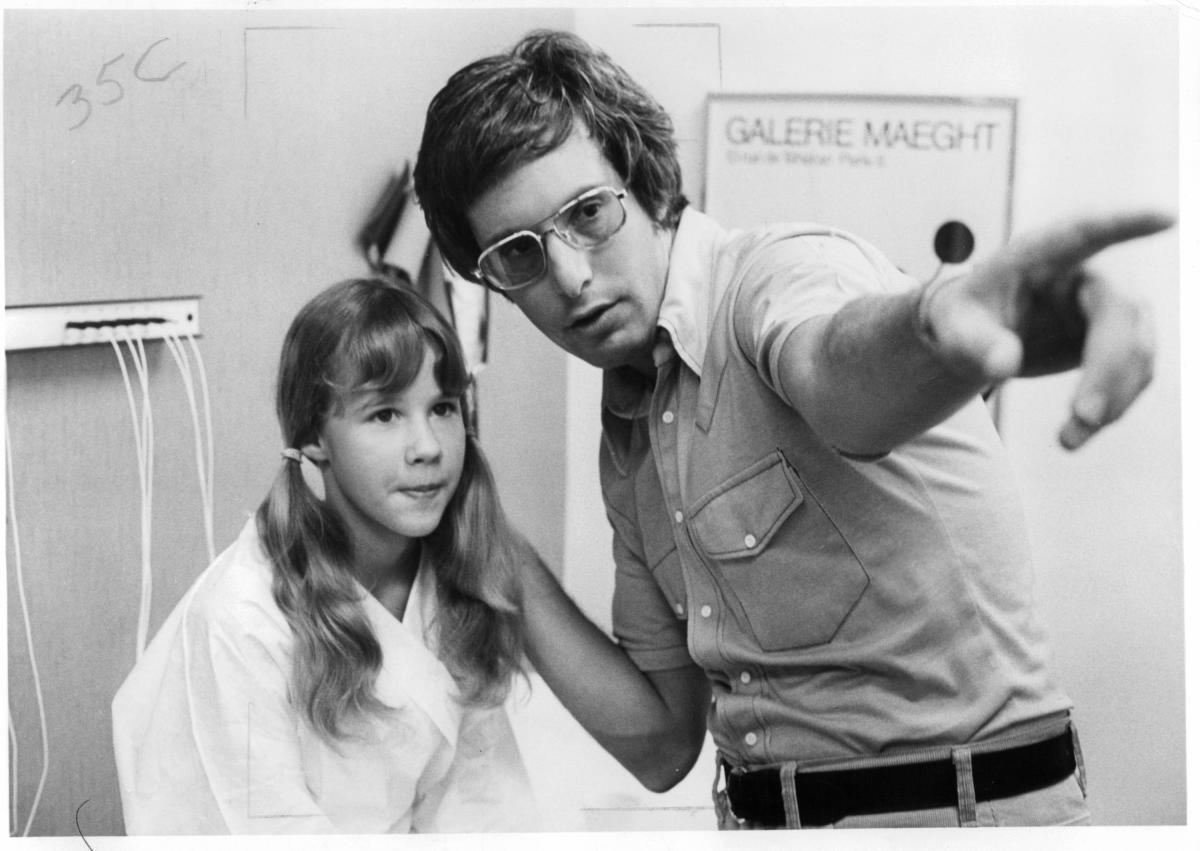 Friedkin gives direction to 12-year-old actress Linda Blair, who played the possessed Regan MacNeil, on the set of The Exorcist.