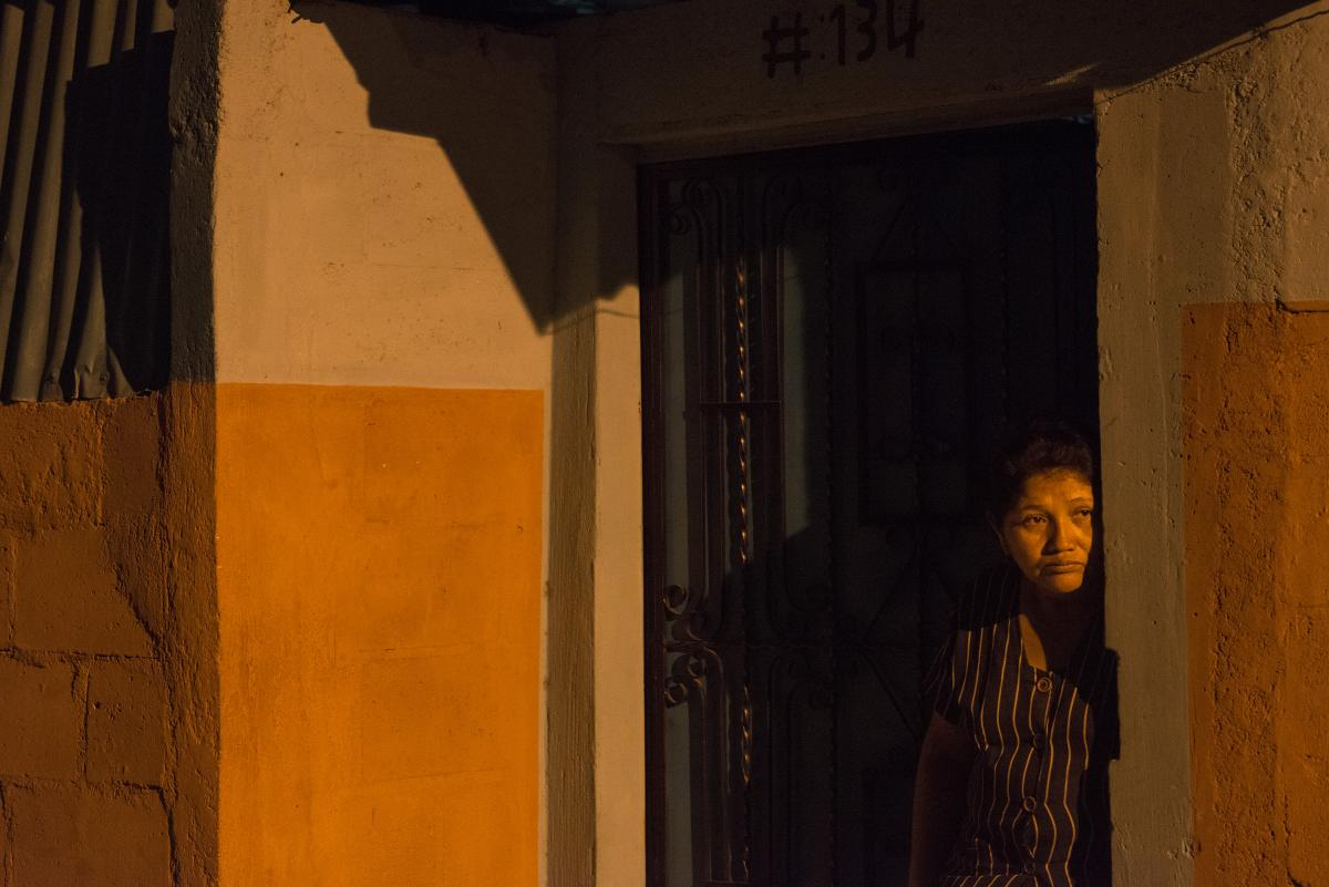 'A resident of Ciudad Delgado gazes at the crime scene in front of her house. A bus driver was shoot at close range causing the bus to crash into the sidewalk. Photo Encarni Pindado'