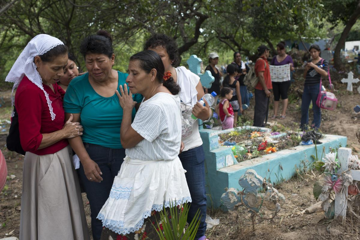 The mother of an assassinated bus driver buries her son at a cemetery on the outskirts of San Salvador.