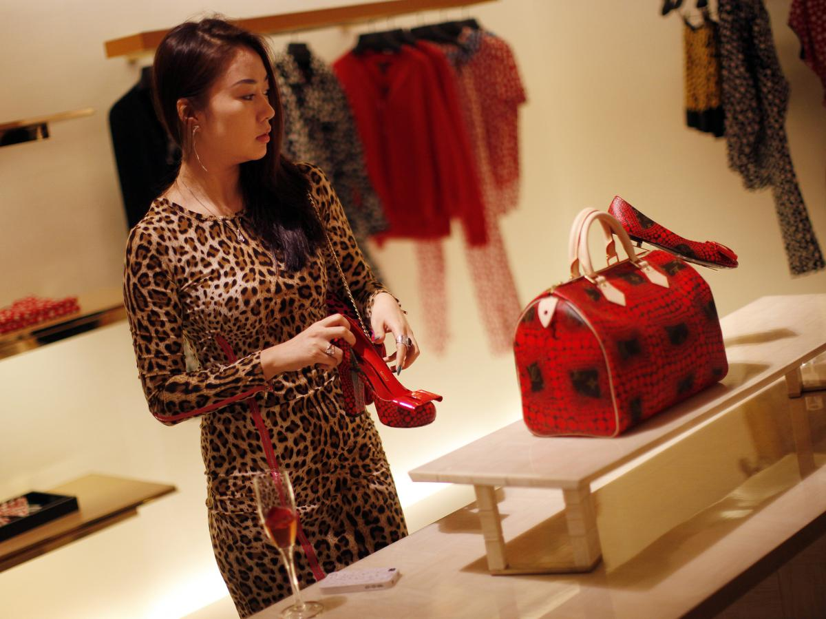 A woman shops in a Louis Vuitton store in downtown Shanghai, on Sept. 7, 2012.