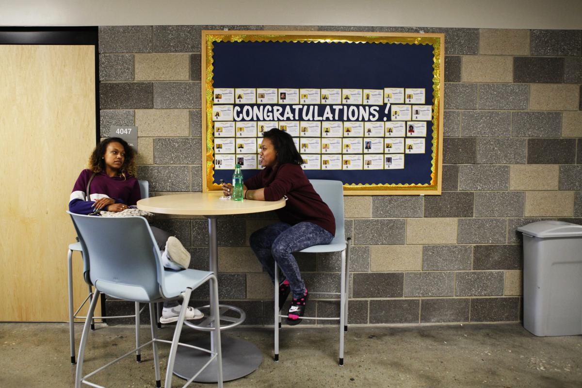 Students sit below a bulletin board of graduation notifications at Scavo Alternative High School in Des Moines, Iowa.