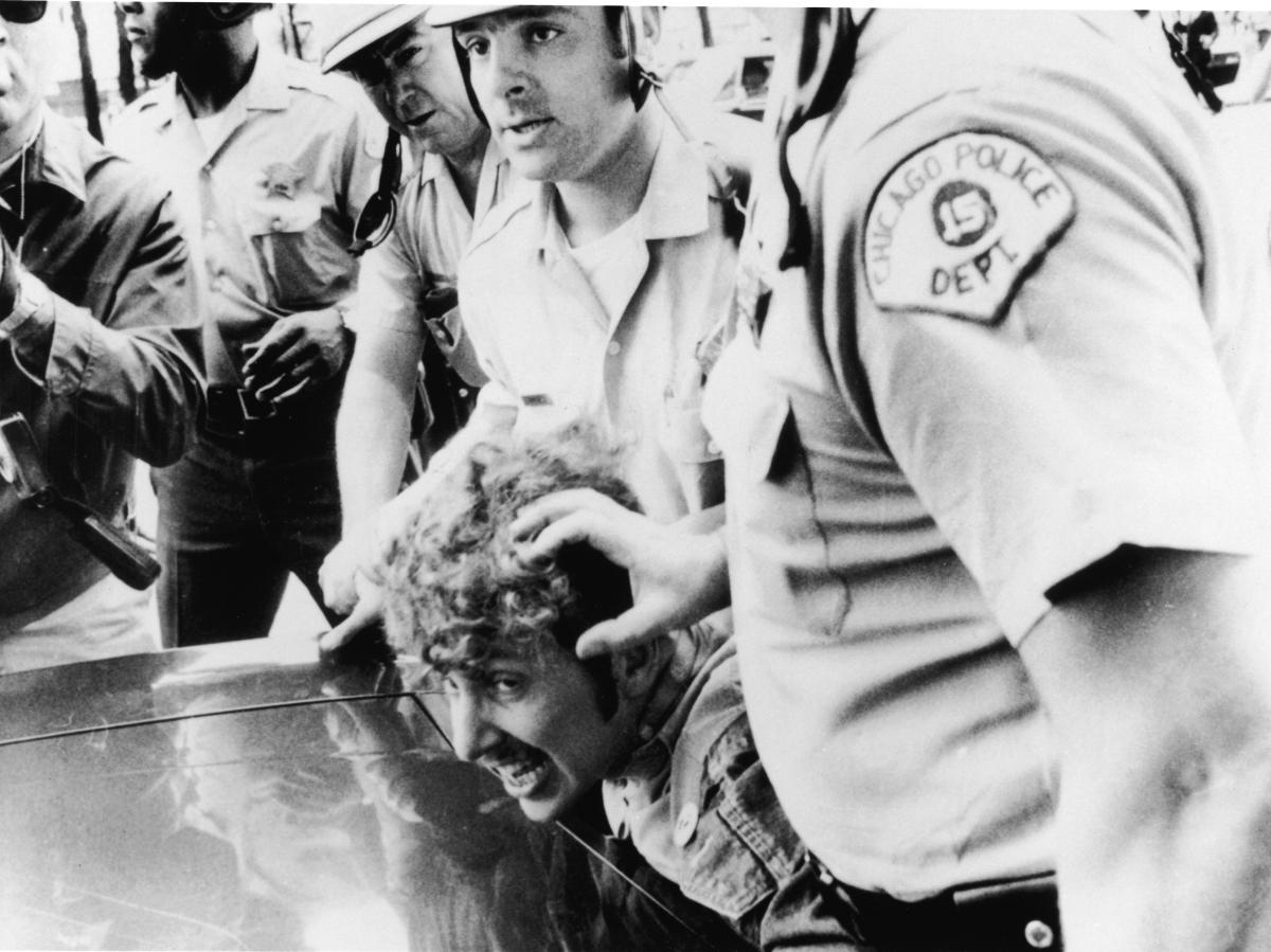 Officers from the Chicago Police Department push a protester's head against the hood of a car after he climbed onto a wooden barricade near the Democratic National Convention and waved a Viet Cong flag during anti-Vietnam War demonstrations in 1968.