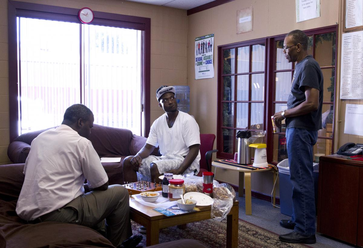David Lee Robinson Jr. (left), a volunteer facilitator, plays chess with Michael Ward at a prison re-entry program site, while Felton Howard, a navigator with the program, looks on. Ward spent more than eight years in the state prison system before his re
