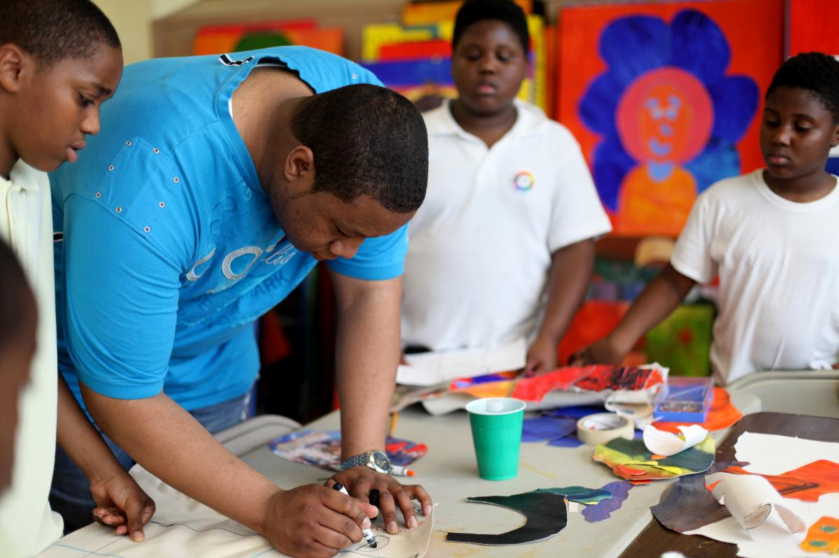 Maurice Kie, a mentor with the program, helps participants brainstorm their life goals. Kie has been with Life Pieces to Masterpieces since he was 9. He was one of the seven first apprentices.