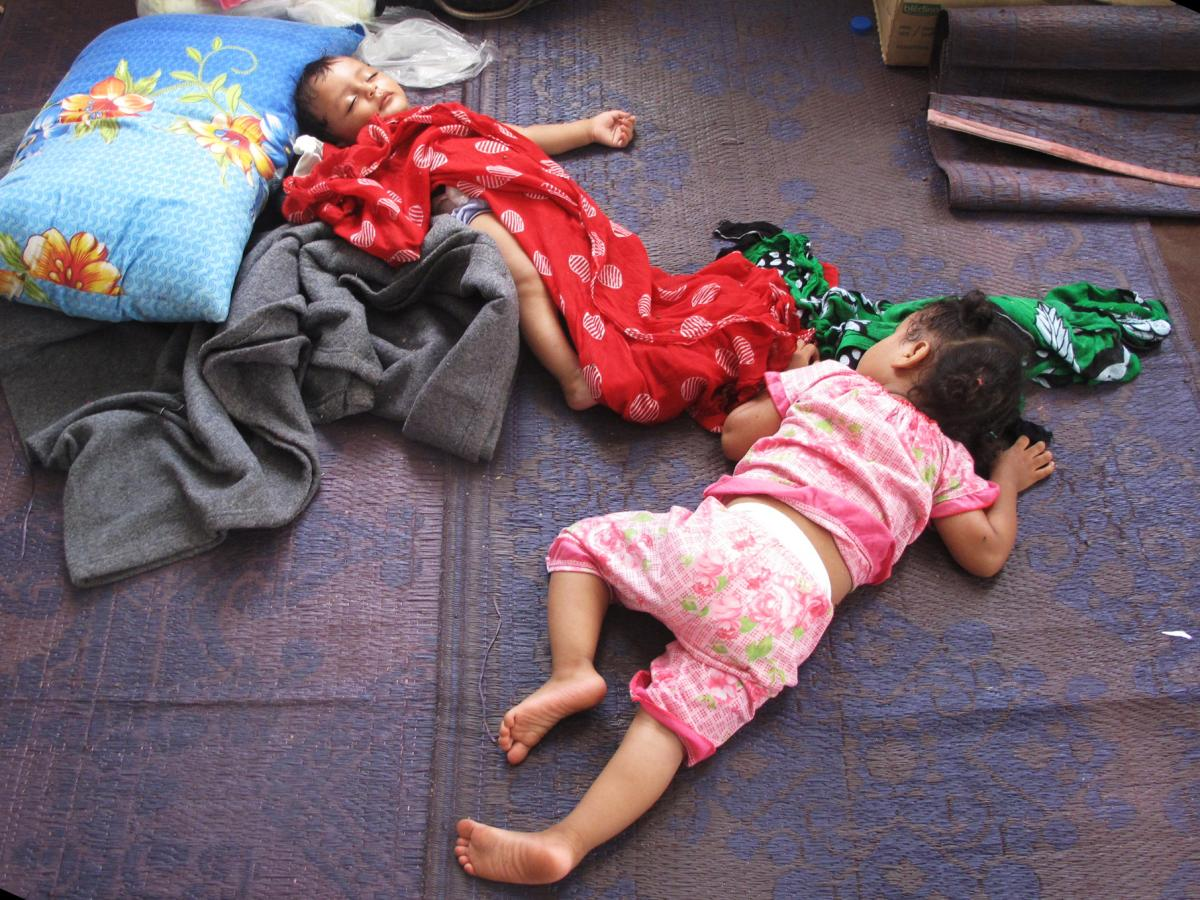 Children nap on the floor of a soccer stadium's warmup room at the Obock port in Djibouti.