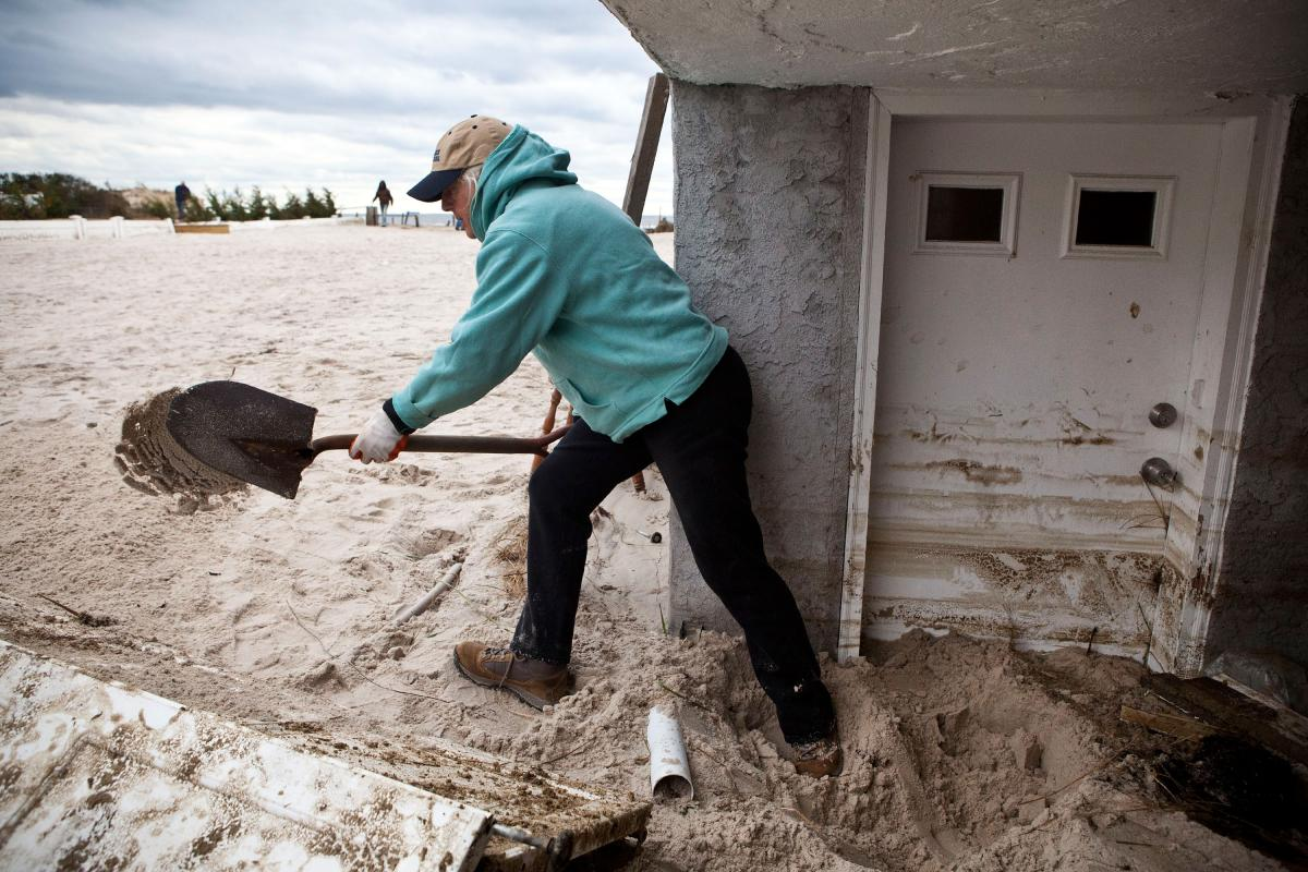Barbara Young tosses sand out her front door in Long Beach, N.Y. The storm caused massive flooding across much of the Eastern Seaboard.