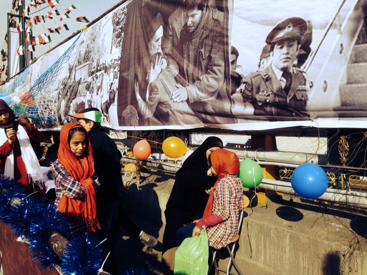 Iranian girls get their faces painted in front of a backdrop of blown-up news images from the 1979 uprising against the U.S.-backed Shah of Iran, in Tehran, on Tuesday.