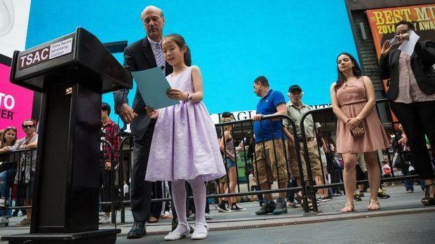 Young artist Sharon Yang told a crowd in Manhattan about her painting — assisted by Times Square Advertising Coalition president Fred Rosenberg, who held the microphone.