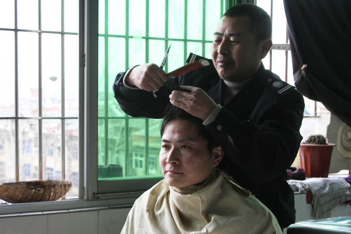 The father of Charles, Shenhua,  cuts his son's hair the day before the wedding.