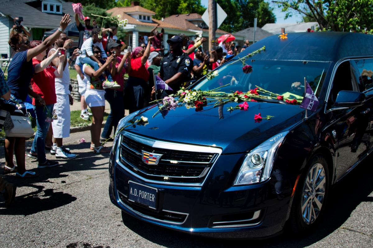 Fans And Mourners Throw Flowers On The Hearse That Carries The Casket