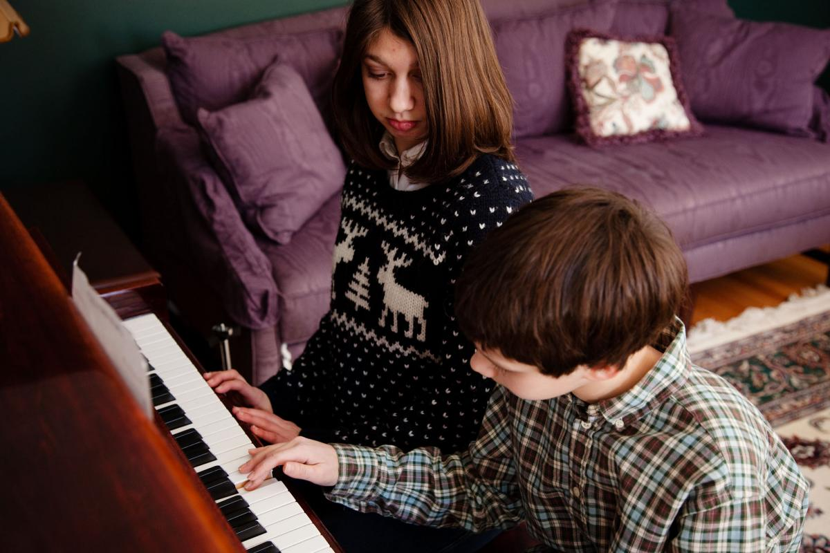 """Samantha watches her brother Nicholas play piano. Their mother says that a new customized voice created by researcher Rupal Patel from a young Samantha's voice sample is happy and has a sweetly familiar quality. """"My son — my son Nicholas — I could hea"""