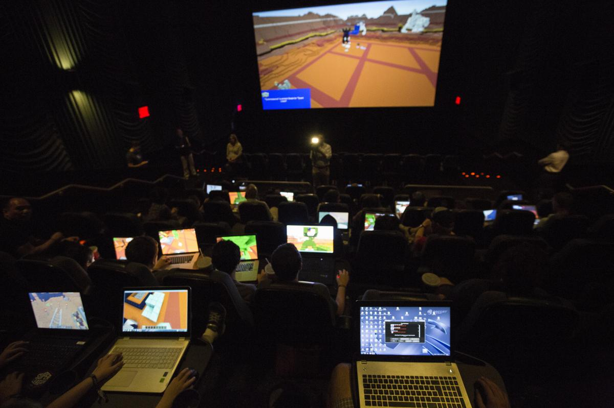 Gamers connect their laptops to the large movie theater screen to play Minecraft together for the Super League Gaming event.