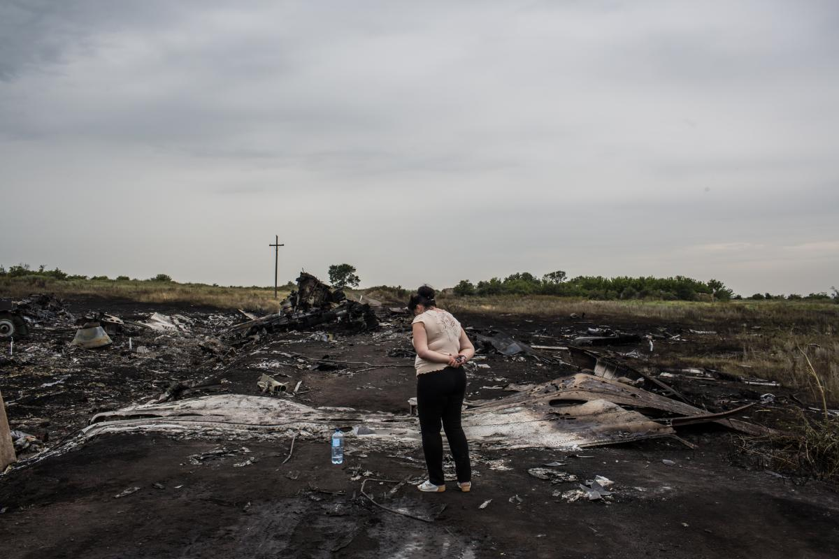 A woman looks at the wreckage in Grabovka. Parts of the crash site were still smoldering Friday.