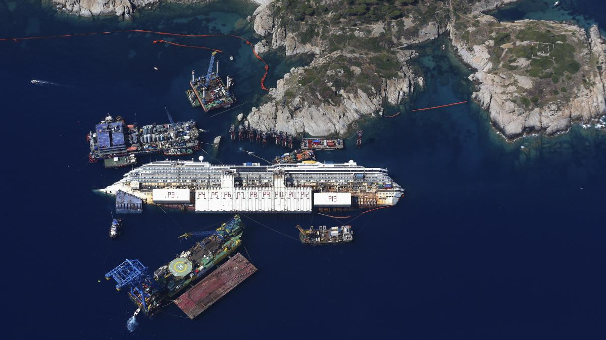 An aerial view taken on Aug. 23 shows the Costa Concordia as it lies on its side next to Giglio Island. The wrecked cruise ship will be rolled off the seabed and onto underwater platforms.