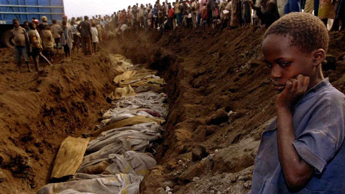 A Rwandan refugee girl stares at a mass grave where dozens of bodies were laid to rest in July 1994.