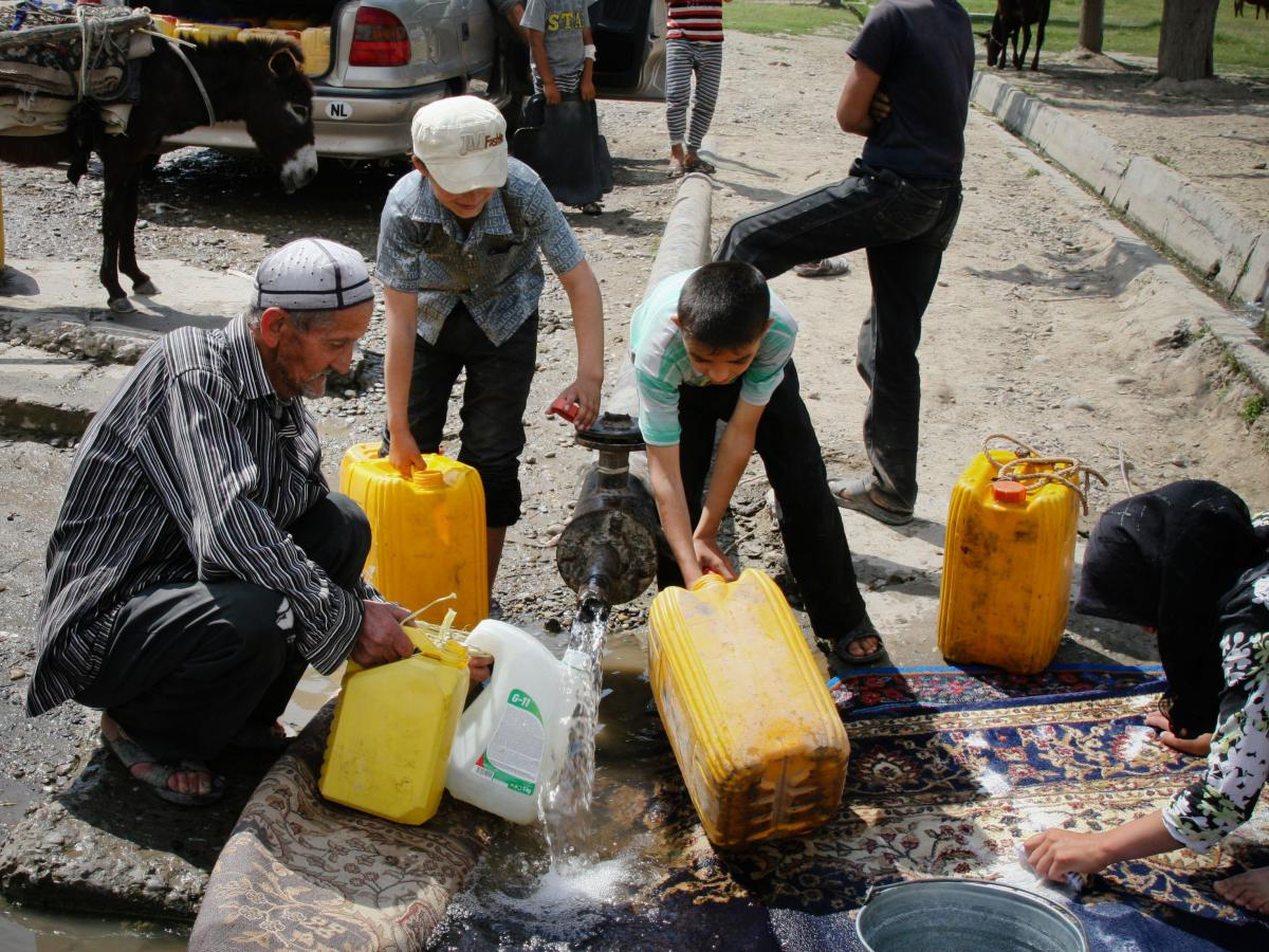 Nazarali Murodov, 66, fills up jerrycans at a broken water pipe in Navbahor, Tajikistan. During the Soviet era, he says, it was easier to get clean, safe water.