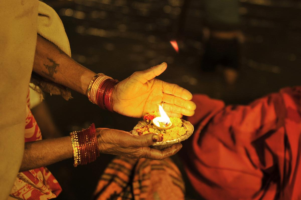 An Indian devotee holds an offering at the Sangam.