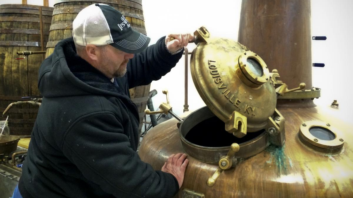 Evan Parker of Turkey Shore Distilleries lifts the distilling kettle's brass door. Parker climbs down this hole between batches to clean the kettle and says he had to measure his hips at first to make sure he'd fit through.
