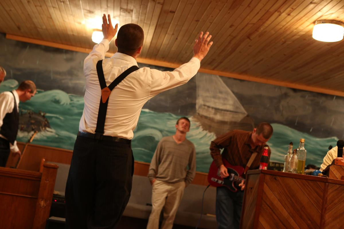 Jacob Grey raises his hands in Pastor Andrew's church.