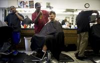 Barber Stan Norwood (center) puts the finishing touches on a cut and style to Mike Fox's hair at the Dennis Barber Shop in Freret, a transitional neighborhood in central New Orleans.