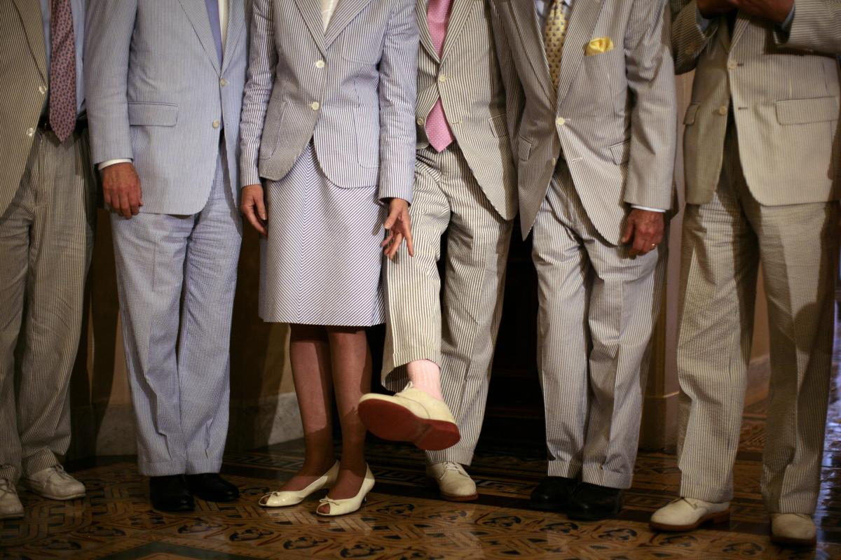 """Then-Sen. Trent Lott, R-Miss., who started """"Seersucker Thursday"""" on Capitol Hill, shows his pink socks that match his tie to fellow senators in June 2007."""