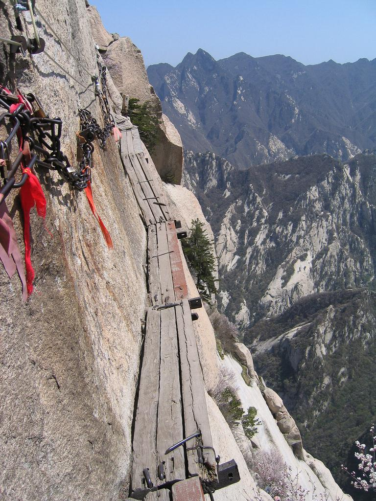 A foot-wide path made of wooden planks winds around the surface of a cliff. Climbers harness themselves to a wire and grab the chain to keep from falling.