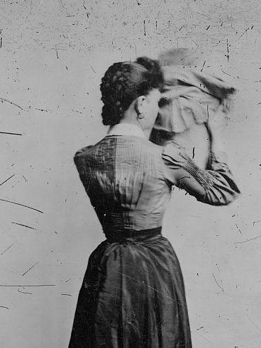Woman holding a bonnet, with her back to camera, between 1880 and 1900.