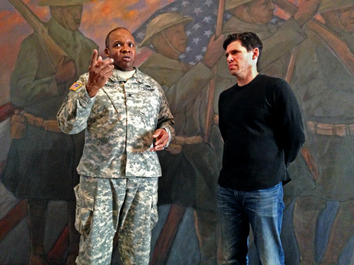 Col. Reginald Sanders, former commander of the 369th Sustainment Brigade, and The Harlem Hellfighters author Max Brooks tour the 369th Regiment Armory in New York City.