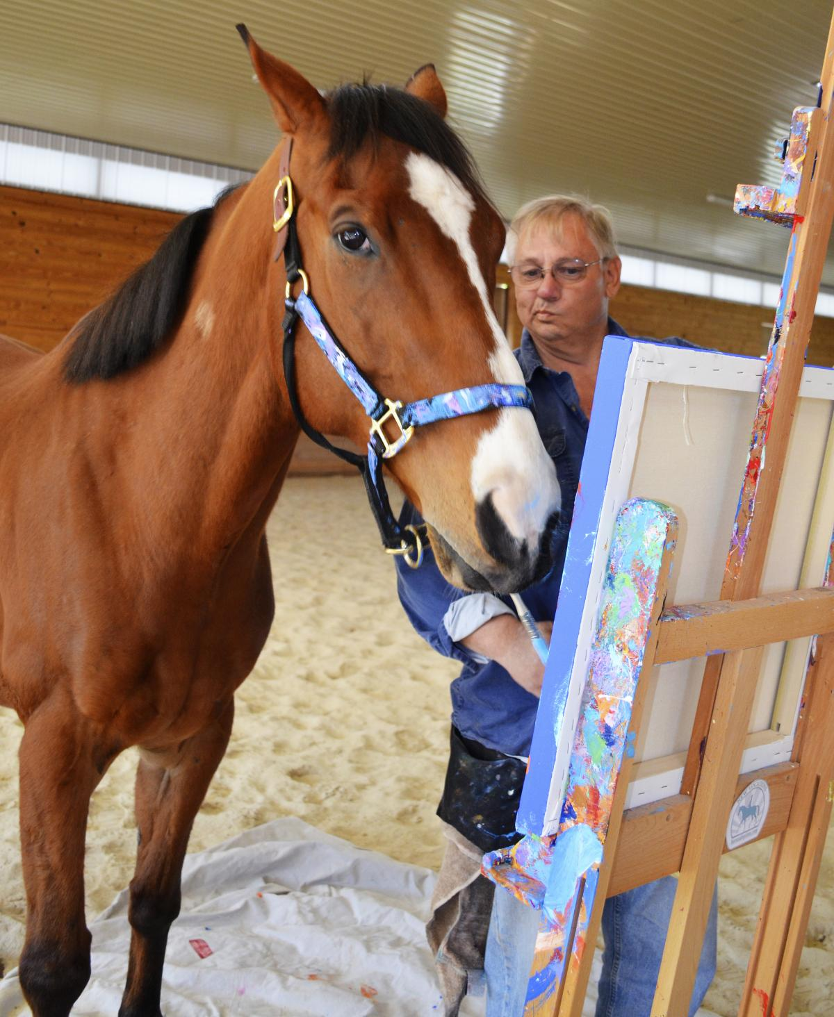Metro wields a paintbrush as owner Ron Krajewski looks on at Motters Station Stables in Rocky Ridge, Md.