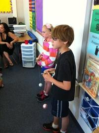 Nine-year-old Logan Tosta and his sister, Avery, show a class of second-graders at Michael J. Castori Elementary School in Sacramento, Calif. how to play with a kendama.